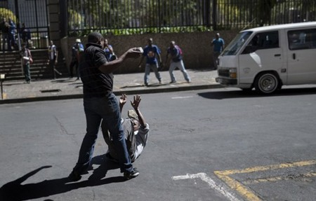 South Africa Is Breaking My Heart, I Cry For My Beloved Country - White Privilidge Racism Rhodes Must Fall Xenophobia A local taxi driver pelts with stones a man on the ground during a confrontation with foreign nationals in the Johannesburg Central Business District on April 15, 2015. Photo: Marco Longari